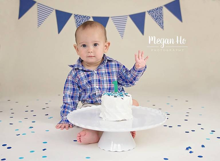 one year boy sitting in front of white cake about to dig in
