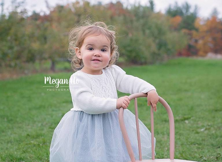 adorable smiling girl in white tutu sweater dress holding chair in nh apple orchard