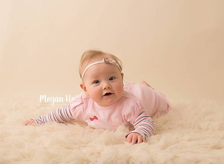 adorable girl in nh studio laying on fuzzy cream rug for four month session
