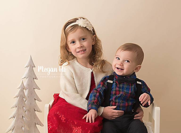 brother and sister sitting on a little bed with white Christmas tree in bedford ng