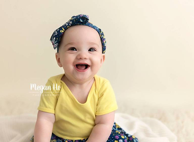close up of smiling 6 month girl face dressed in yellow in southern nh session