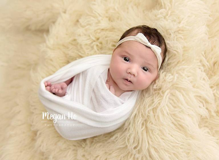 wrapped and awake newborn baby girl on rug in bedford nh studio
