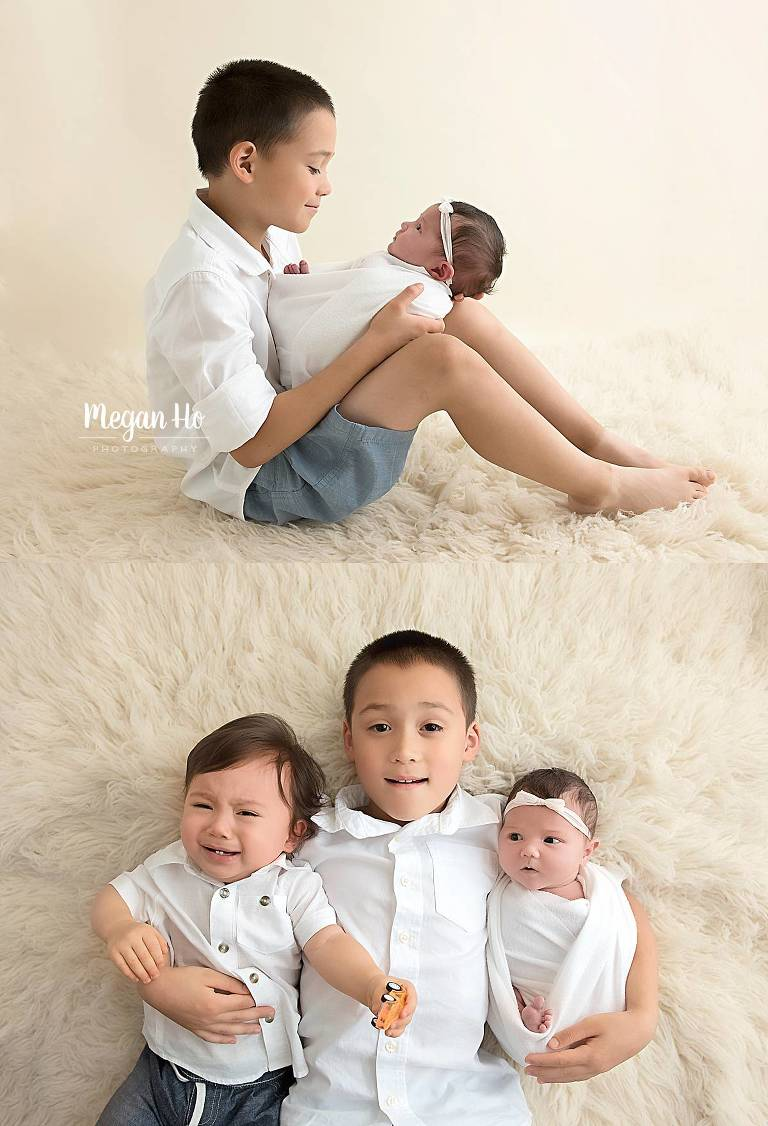 Big brother siblings with adorable baby sister on white rug