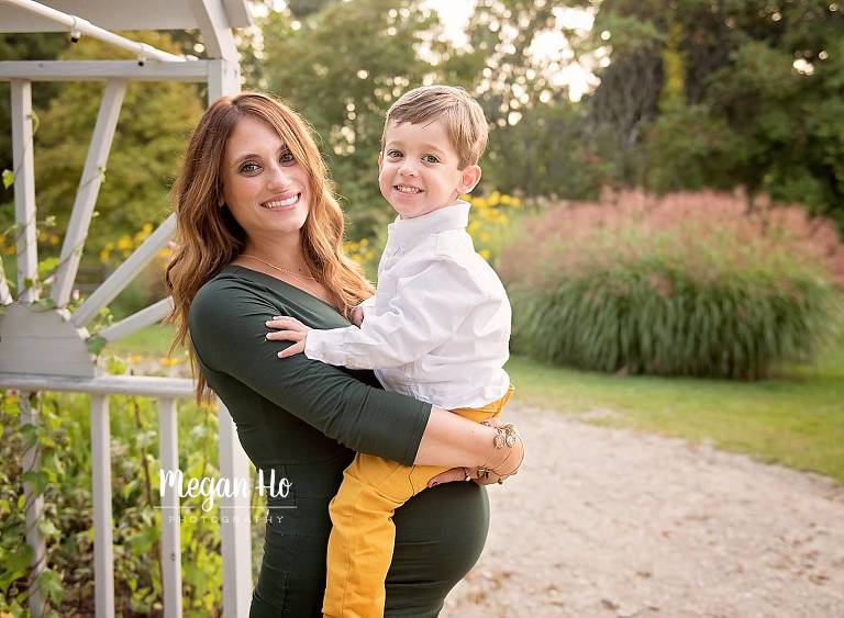 glowing mom to be with her little boy smiling in Hollis nh park session
