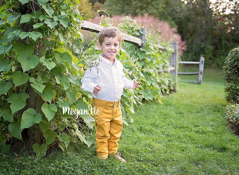 little two year old boy standing in front of ivy fence with yellow pants
