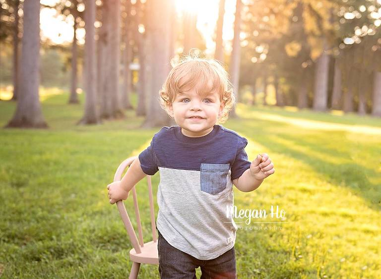 golden light above little boys head smiling with blue and grey shirt