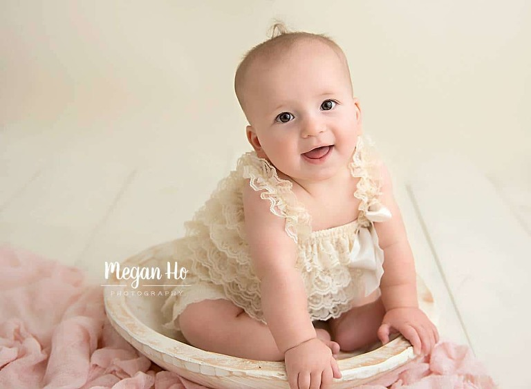 six month girl sitting in white bowl in cream lace romper with curl on top of head