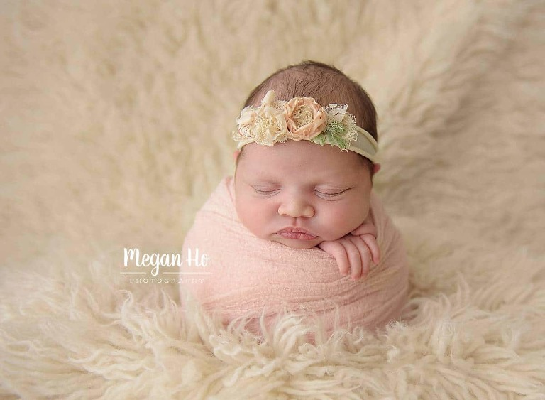 baby girl in potato sack wrapped in blush pink in New Hampshire studio