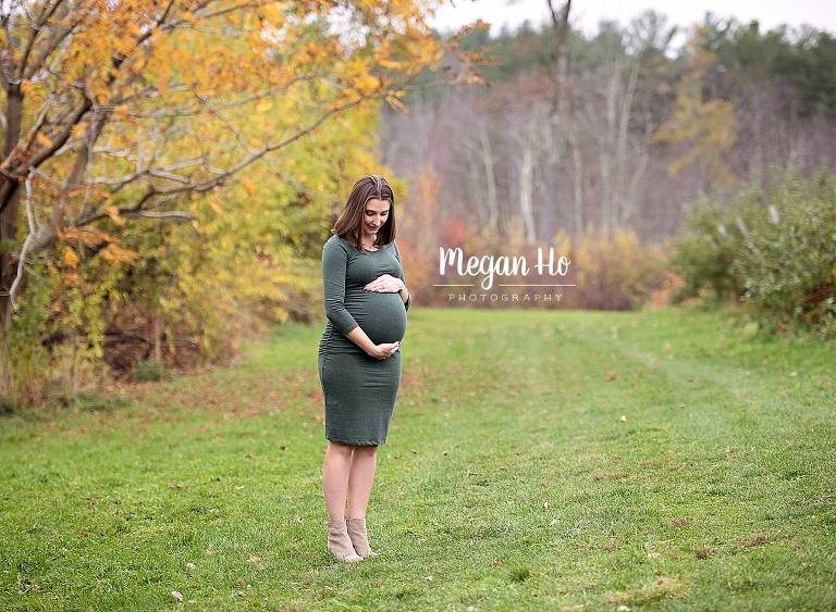 mom to be looking down at her belly in tight green dress in apple orchard