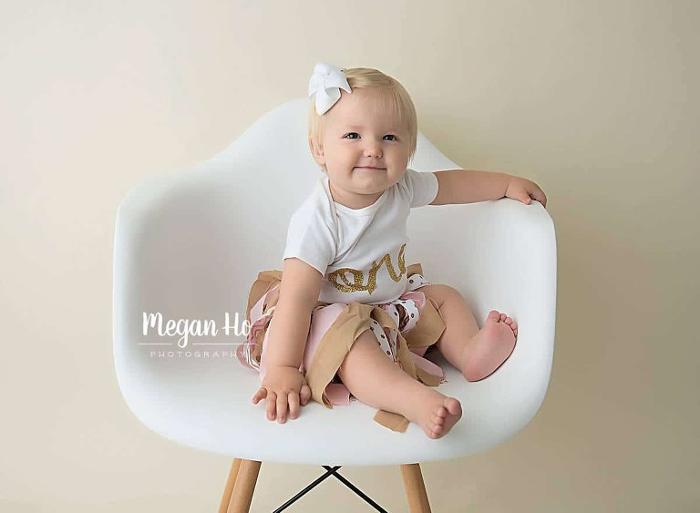 smiling one year blonde girl in white chair in bedford nh studio