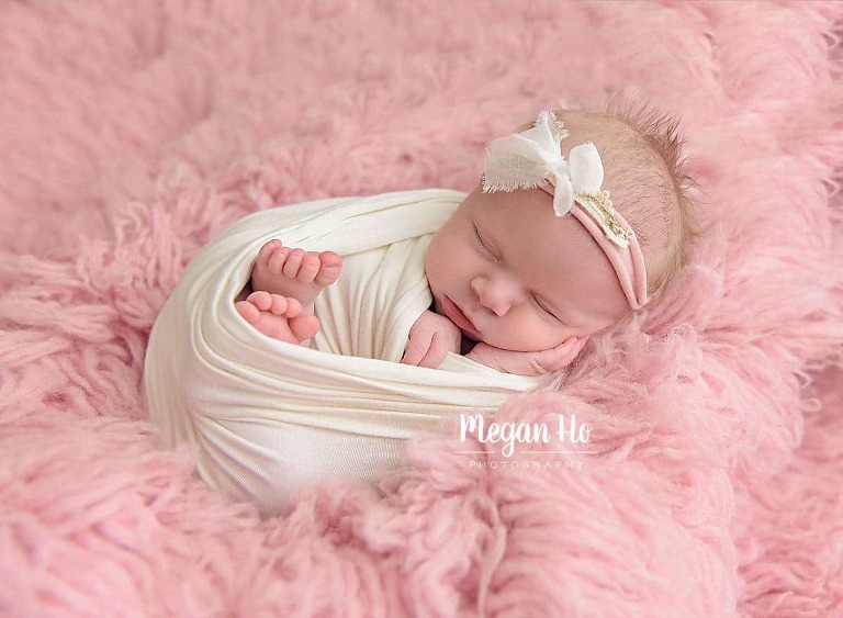 baby girl wrapped in white wrap snuggled on pink fluffy rug sleeping in nh